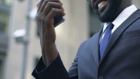 Homme d'affaires satisfait de l'appli d'organisateur sur son smartphone, lisant de bonnes nouvelles banque de vidéos