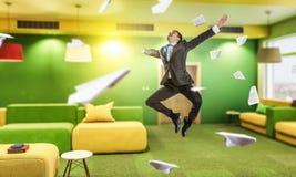 Homme d'affaires sautant dans le bureau Media mélangé Photos stock