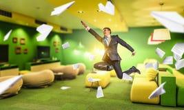 Homme d'affaires sautant dans le bureau Media mélangé Photographie stock