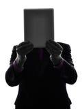 Homme d'affaires se cachant derrière la silhouette numérique de comprimé Image stock