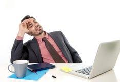 Homme d'affaires se penchant sur la chaise fonctionnant à l'ordinateur portable d'ordinateur de bureau semblant satisfaisant et d image stock