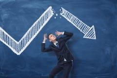 Homme d'affaires se recroquevillant sur le fond bleu de tableau noir avec le dessin de craie de la flèche blanche de statistique  Photographie stock libre de droits