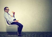 Homme d'affaires se sentant fatigué et somnolent après consommation de trop d'hamburgers pour le déjeuner photographie stock