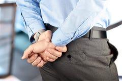 Homme d'affaires se tenant avec des mains derrière le sien de retour Image stock