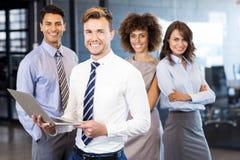 Homme d'affaires se tenant avec un ordinateur portable et une équipe se tenant à l'arrière-plan Image stock