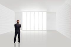 Homme d'affaires se tenant dans une salle vide Images stock