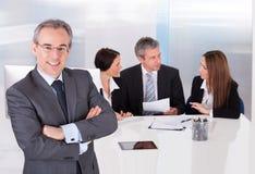 Homme d'affaires se tenant devant ses collègues Photos stock