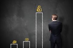 Homme d'affaires se tenant devant un tableau noir avec un diagramme Image stock