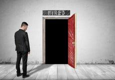 Homme d'affaires se tenant devant une porte ouverte avec l'obscurité derrière elle Photos stock