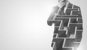 Homme d'affaires se tenant et pensant avec le labyrinthe Photo stock