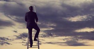 Homme d'affaires se tenant sur l'échelle haute en ciel Concept d'affaires Image stock