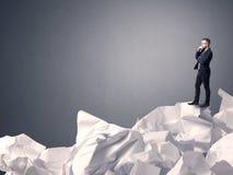 Homme d'affaires se tenant sur le papier chiffonné Image stock