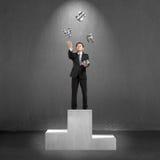 Homme d'affaires se tenant sur le podium jetant et attrapant l'argent 3D sy Photo libre de droits