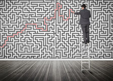 Homme d'affaires se tenant sur une échelle résolvant le puzzle de labyrinthe photo stock