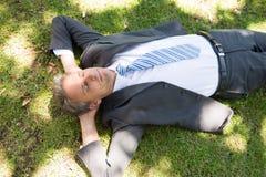 Homme d'affaires se trouvant sur l'herbe photographie stock libre de droits