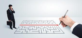 Homme d'affaires semblant la solution actuelle de dessin pour le labyrinthe Photographie stock