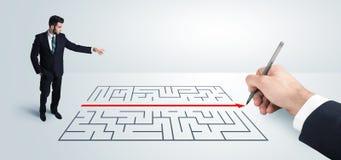 Homme d'affaires semblant la solution actuelle de dessin pour le labyrinthe Photo stock