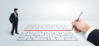 Homme d'affaires semblant la solution actuelle de dessin pour le labyrinthe Image libre de droits