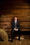 Homme d'affaires seul s'asseyant sur le banc près de la meule de foin photos libres de droits