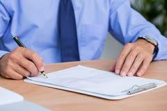 Homme d'affaires signant un contrat dans le bureau Images stock