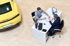 Homme d'affaires Signing Papers pour acheter la voiture photographie stock