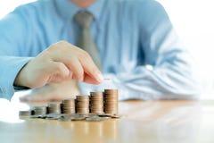 Homme d'affaires Sitting au bureau et aux pièces de monnaie Photographie stock libre de droits