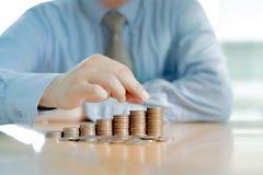 Homme d'affaires Sitting au bureau et aux pièces de monnaie Image libre de droits