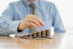 Homme d'affaires Sitting au bureau et aux pièces de monnaie Images libres de droits