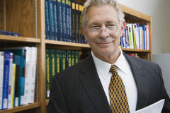 Homme d'affaires Smiling While Standing dans la bibliothèque Image stock