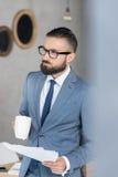 Homme d'affaires songeur avec la tasse et les papiers de café dans des mains dans le bureau Image libre de droits