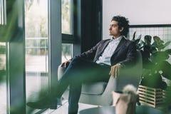 homme d'affaires songeur dans le costume se reposant dans le fauteuil et regardant la fenêtre Image libre de droits