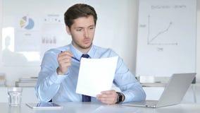Homme d'affaires songeur Reading Documents au travail clips vidéos