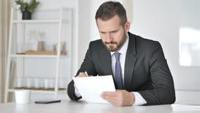 Homme d'affaires songeur Reading Documents dans le bureau, écritures banque de vidéos
