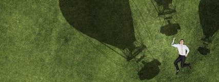 Homme d'affaires songeur sur l'herbe image stock