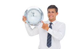 Homme d'affaires soucieux tenant et montrant une horloge photos libres de droits