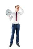 Homme d'affaires soucieux tenant une horloge images stock