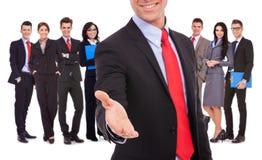 Homme d'affaires souhaitant la bienvenue à l'équipe avec la prise de contact Photographie stock