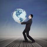 Homme d'affaires soulevant la planète de la terre photographie stock libre de droits