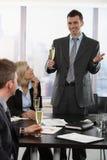 Homme d'affaires soulevant le pain grillé avec le champagne Photographie stock libre de droits