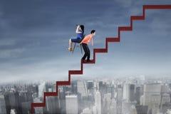 Homme d'affaires soulevant son collègue sur l'escalier rouge Image libre de droits