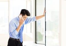 Homme d'affaires soumis à une contrainte parlant au téléphone dans le bureau Photos libres de droits