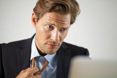 Homme d'affaires soumis à une contrainte travaillant sur l'ordinateur portable Image libre de droits