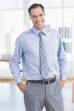 Homme d'affaires souriant à l'appareil-photo avec des mains sur sa poche Photos libres de droits