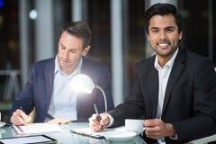 Homme d'affaires souriant à l'appareil-photo tandis qu'écriture de collègue sur le papier Images stock