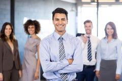 Homme d'affaires souriant à l'appareil-photo tandis que ses collègues posant à l'arrière-plan Photographie stock