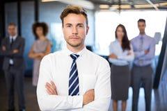 Homme d'affaires souriant à l'appareil-photo tandis que ses collègues se tenant à l'arrière-plan Photographie stock libre de droits