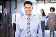Homme d'affaires souriant à l'appareil-photo tandis que ses collègues se tenant à l'arrière-plan Image libre de droits