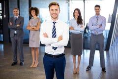 Homme d'affaires souriant à l'appareil-photo tandis que ses collègues se tenant à l'arrière-plan Photographie stock