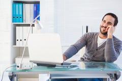 Homme d'affaires souriant à l'appareil-photo travaillant sur l'ordinateur portable images stock