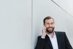 Homme d'affaires souriant comme il cause sur son mobile Image libre de droits